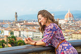 Happy young woman writing sms against panoramic view of florence