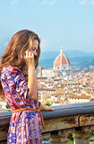 Young woman talking cell phone against panoramic view of florenc