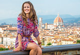 Happy young woman sitting against panoramic view of florence, it