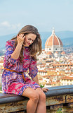 Young woman sitting against panoramic view of florence, italy