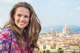 Portrait of happy young woman against panoramic view of florence
