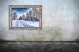 Old wooden frame with beautiful winter landscape on dirty wall