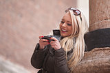 blonde girl outdoors with her mobile phone