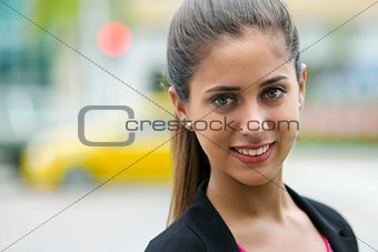 Portrait of business woman on street with cars and traffic light
