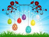 Dangling Easter eggs on blue sky landscape