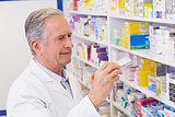 Senior pharmacist taking medicine from shelf