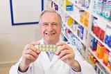 Senior pharmacist holding up blister packs