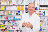 Smiling pharmacist holding a box of pills
