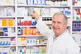 Smiling pharmacist taking medicine from shelf