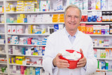 Senior pharmacist holding bowl of medicines