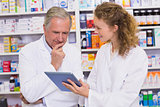 Team of pharmacist looking at tablet pc
