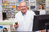 Pharmacist holding medicines looking at camera