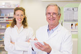 Pharmacist and his colleague with arms crossed behind