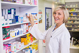 Junior pharmacist taking medicine from shelf