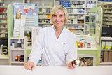 Smiling pharmacist holding medicine jar