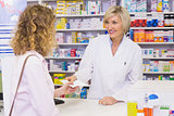 Customer handing a prescription to a smiling pharmacist