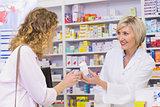 Smiling pharmacist holding a medicine jar