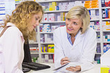 Pharmacist showing prescription to a customer