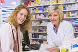 Pharmacist and costumer looking at camera