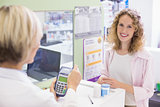 Pharmacist using card machine