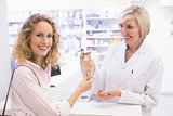 Pharmacist giving bag paper to costumer