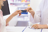 Pharmacist giving credit card to costumer