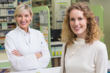 Pharmacist and customer looking at camera