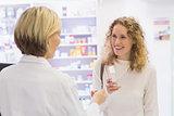 Costumer showing medicine jar to pharmacist