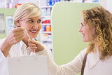 Pharmacist and costumer holding paper bag