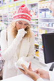 Sick girl with scarf and colorful hat giving bottle of drug