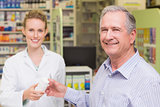 Pharmacist and costumer smiling a camera