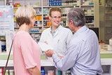 Pharmacist giving prescription to costumer