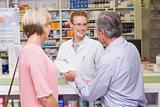 Pharmacist giving prescription to costumer