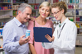 Pharmacist showing clipboard to costumers