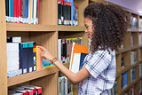 Student picking a book from shelf in library