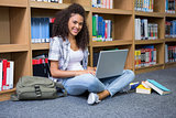 Student sitting on floor in library using laptop