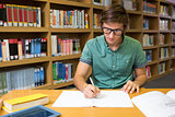 Student sitting in library writing