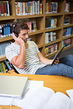 Student listening music in the library with tablet