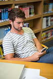 Student listening music in the library with smartphone
