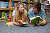 Students reading book lying on library floor