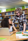 Student getting help from classmate in library