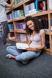 Pretty student sitting on floor reading book in library