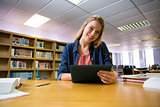 Student studying in the library with tablet