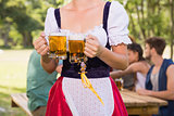 Pretty oktoberfest girl holding beer tankards