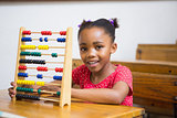Smiling pupil using abacus in classroom