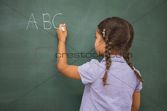 Pupil writing letters on a blackboard