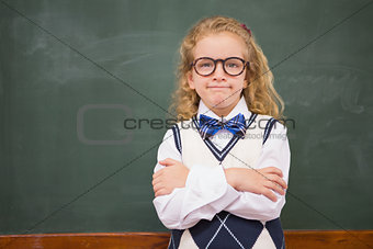 Perplex pupil looking at camera with arms crossed