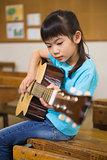 Cute pupil playing the guitar
