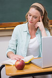 Teacher reading book at her desk