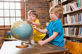 Cute pupils looking at globe
